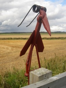 A bird sculpture on a path side fence